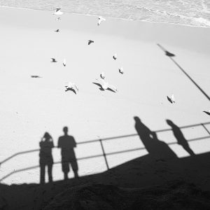 Two people stand with shadows on beach